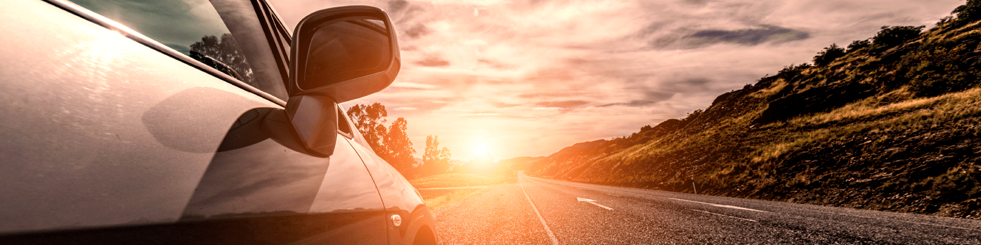 Image of a car driving down a highway with mountains on the right side and the sun setting.